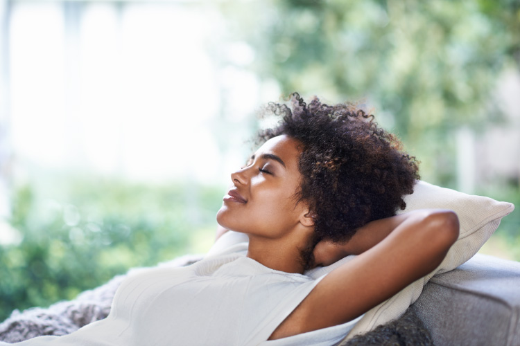 Curly-haired women reclines and relaxes without dental anxiety
