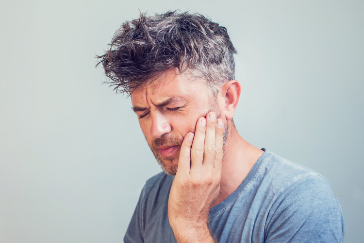 Middle-aged man with sensitive teeth cringes in pain and touches his cheek