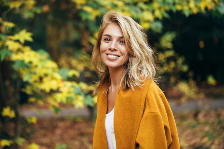 Blonde woman with dental veneers smiles while wearing a mustard yellow pea coat outside by fall leaves