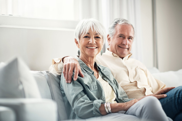 Older couple with dental implants smiles while sitting on the couch