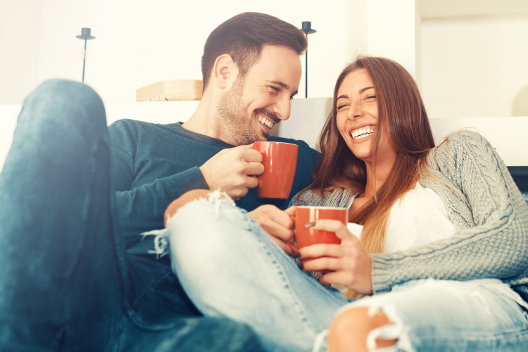 Brunette couple with CEREC crowns smiles while drinking from mugs on a couch