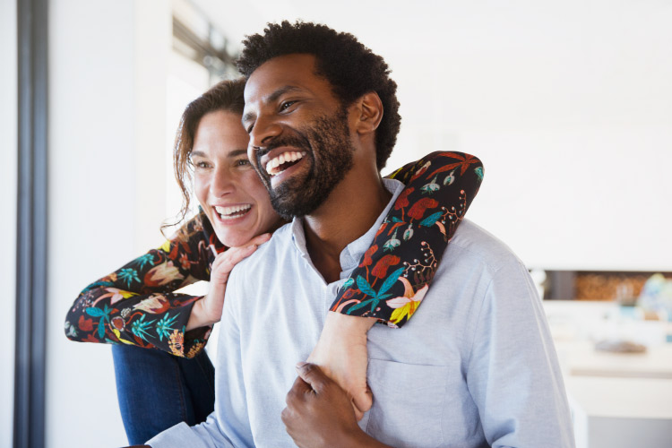 Dark-haired man and woman embrace and smile because they have overcome their dental anxiety together