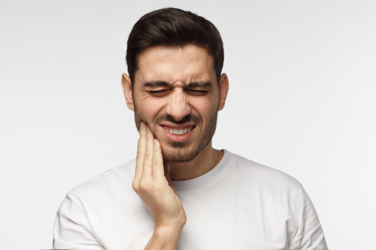 Brunette man cringes in pain due to toothache dental emergency