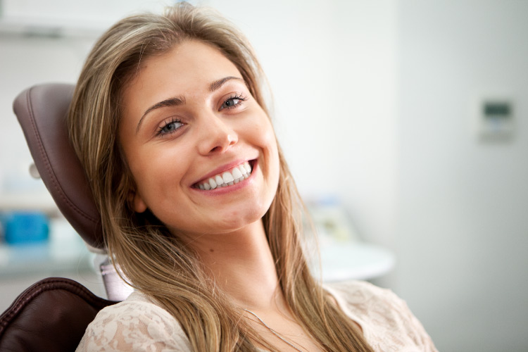 Brunette woman at the dentist smiles after getting her chipped tooth fixed