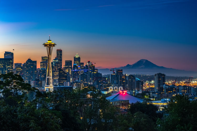 Dusk skyline photo of Seattle, WA, showing many landmarks and attractions, including the Space Needle and Mount Rainier,