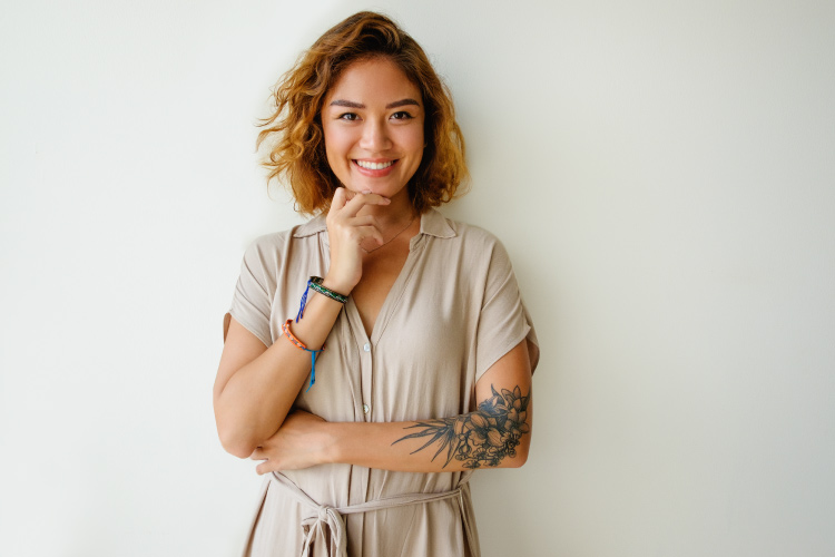 Brunette woman with an arm tattoo smiles with dental implants that have restored her smile in 2020