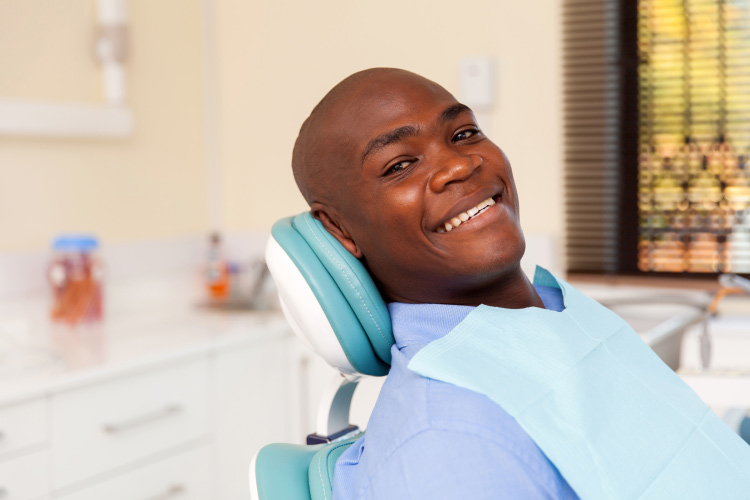 Bald patient smiles in the dental chair before his oral surgery after given tips to manage his pain