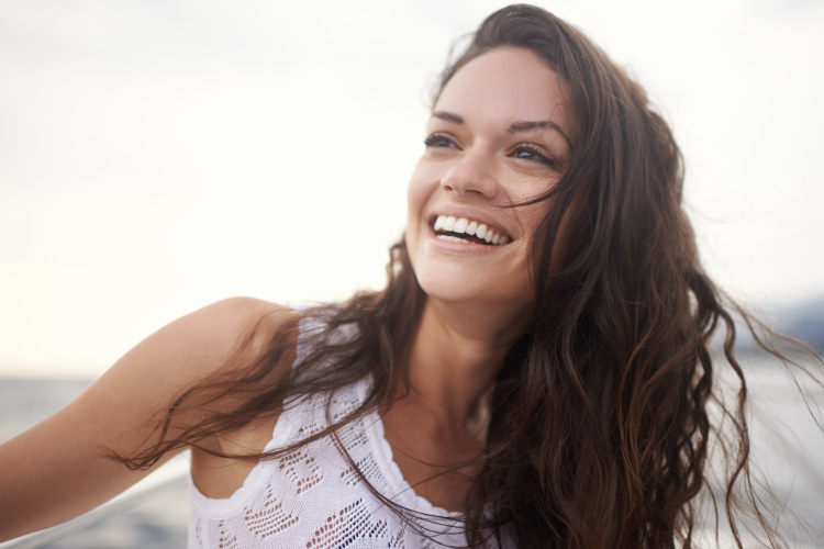 Brunette woman smiles in the Pacific Northwest after receiving holistic dentistry at Optima Dental Spa