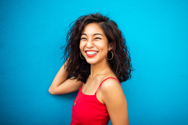 Dark-haired woman in a red tank top smiles against a blue wall after ZOOM! teeth whitening