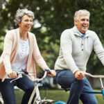 A husband and wife with snap-on dentures and dental implants smile as they ride bikes together