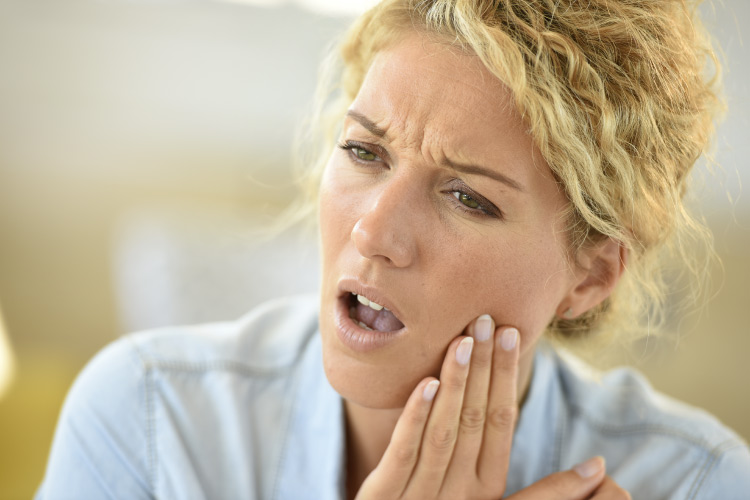 Blonde woman after oral surgery cringes in pain and touches her cheek