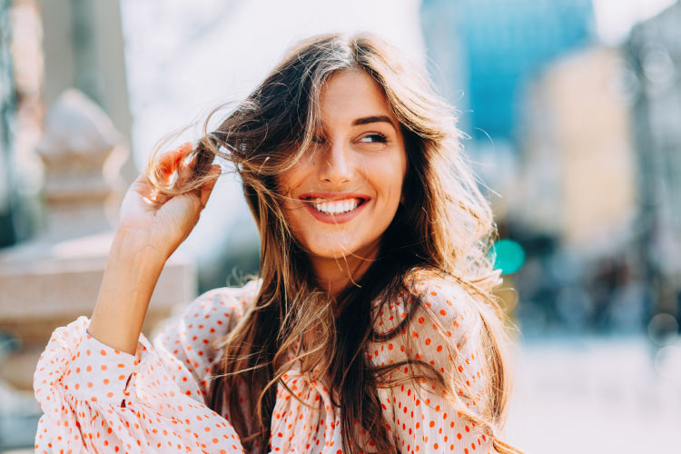 Brunette woman with sensitive teeth smiles because she safely whitened her teeth at Optima Dental Spa
