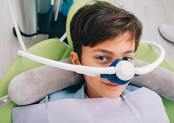 young boy sitting in a dental chair with a sedation mask on his face