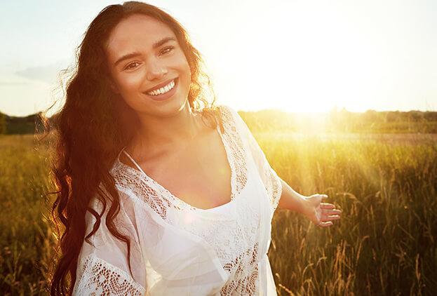 Woman smiling outside in a field