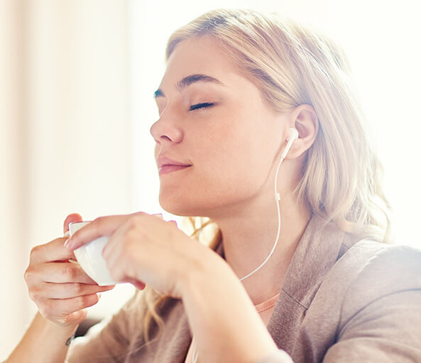 woman relaxing while listening to music and drinking a cup of tea