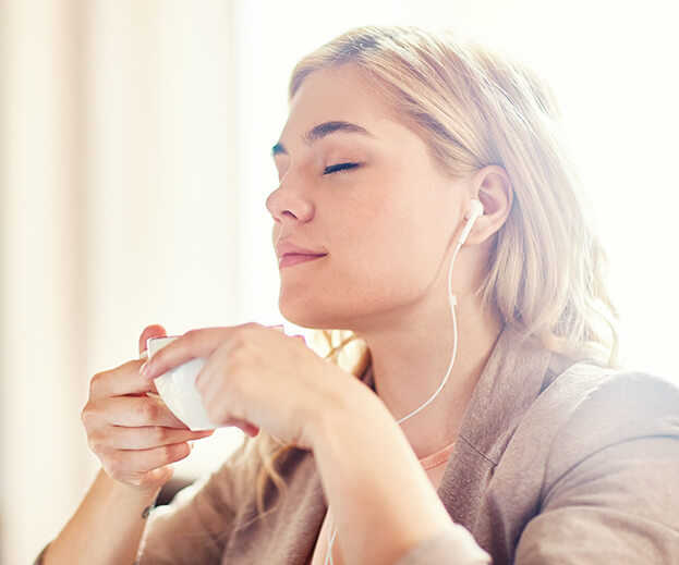 young woman relaxing while sipping a cup of tea and listening to music through earbuds