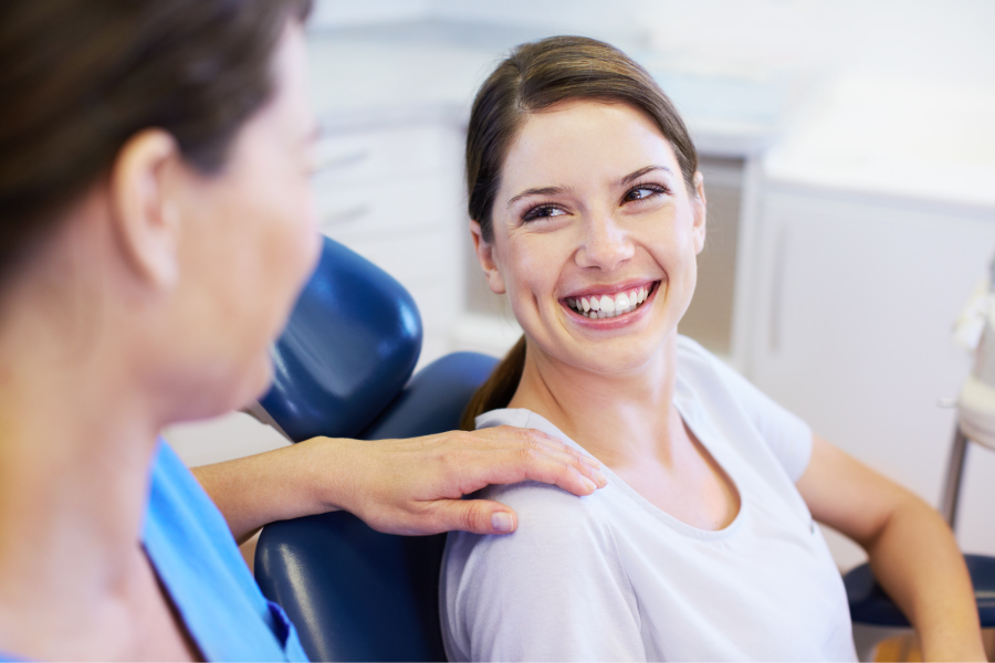 Brunette woman in a dental chair smiles because she is relaxed at the dentist