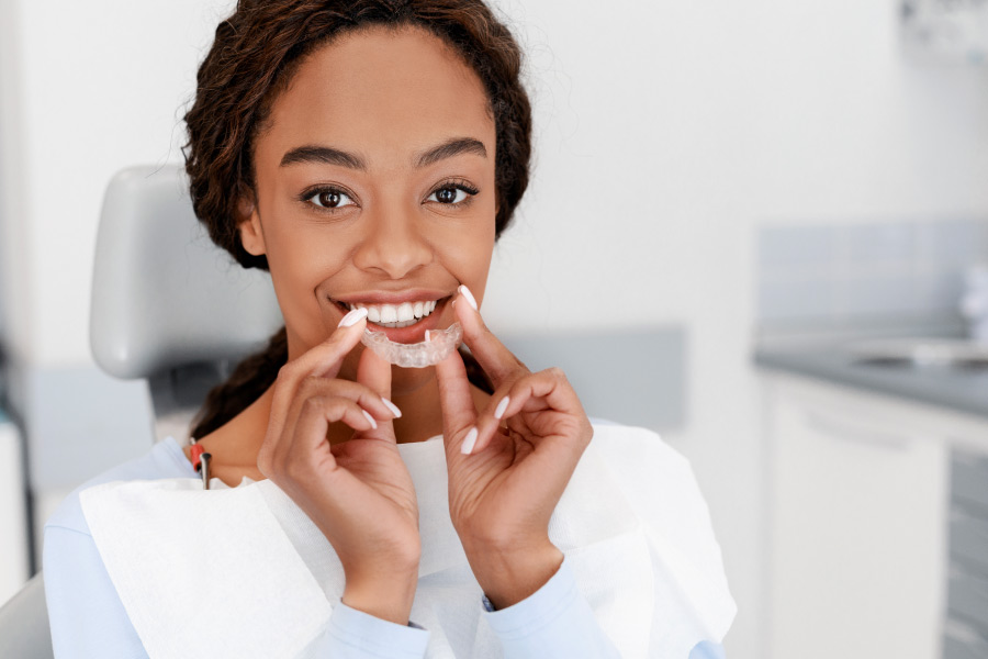 Brunette woman smiles as she puts in her ClearCorrect aligners to straighten her teeth