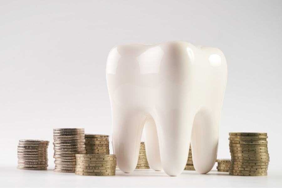 A tooth next to piles of coins to depict how to pay for dental care at Optima Dental Spa