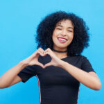Curly-haired woman in a black shirt against a blue wall smiles and makes a heart shape for Optima Dental Spa