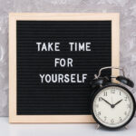 "Letter board that says ""Take Time for Yourself"" next to a clock and a gray wall"