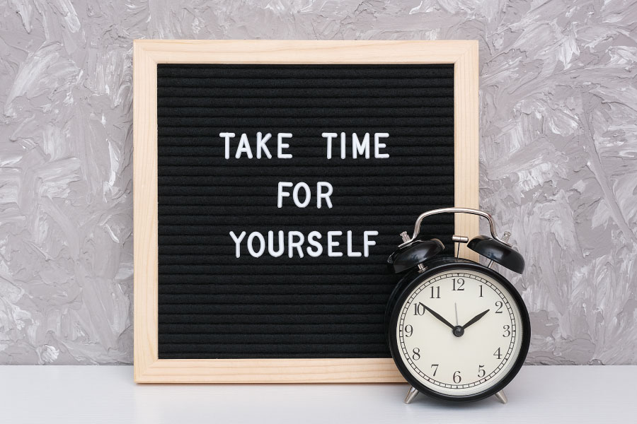"""Letter board that says """"Take Time for Yourself"""" next to a clock and a gray wall"""