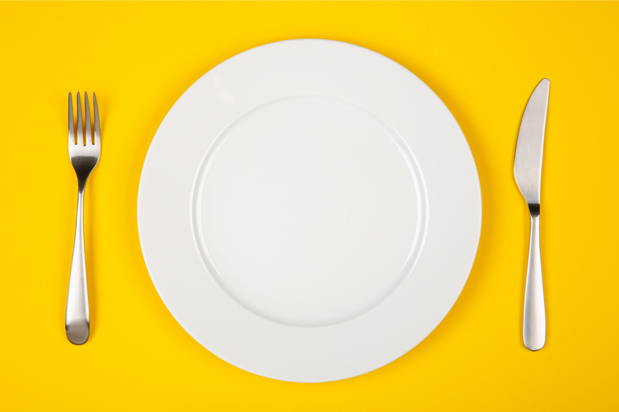 Aerial view of a white plate and silverware against a yellow table