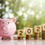 A pink piggy bank next to 2020 on coins to indicate your dental insurance benefits this year
