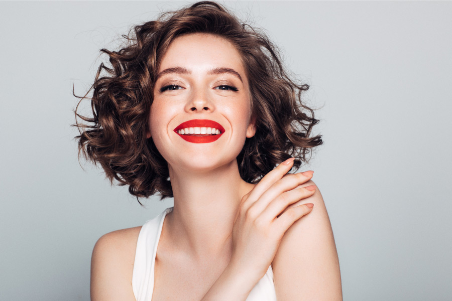 Brunette woman with red lipstick smiles after receiving safe BOTOX at the dentist