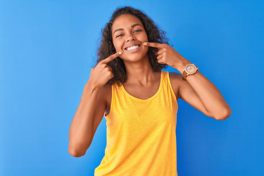 Brunette woman in a yellow tanktop smiles and points at her teeth after her cosmetic consultation