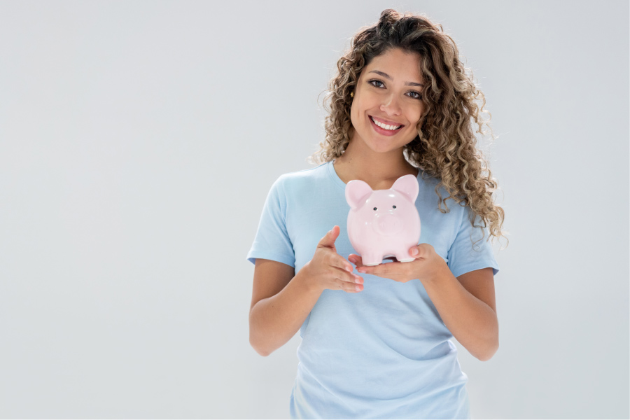 Curly-haired woman in a blue shirt smiles as she holds a piggy bank to discuss Optima Dental Spa's Dental Savers Plan