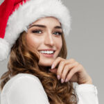 Brunette woman smiles while wearing a red Santa hat for Christmas