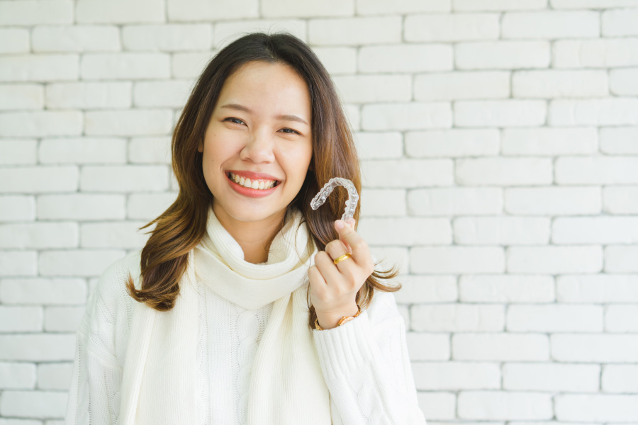 Brunette woman smiles as she holds up her ClearCorrect aligners to straighten her teeth