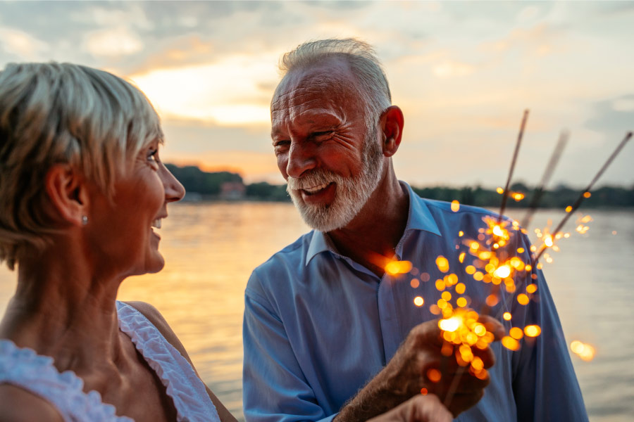 A couple celebrates the New Year with sparklers and a full-mouth reconstruction at Optima Dental Spa