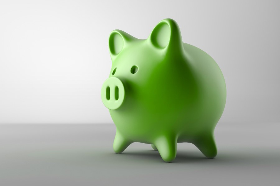 Green piggy bank on a gray counter for a post about the Dental Savings Plan at Optima Dental Spa