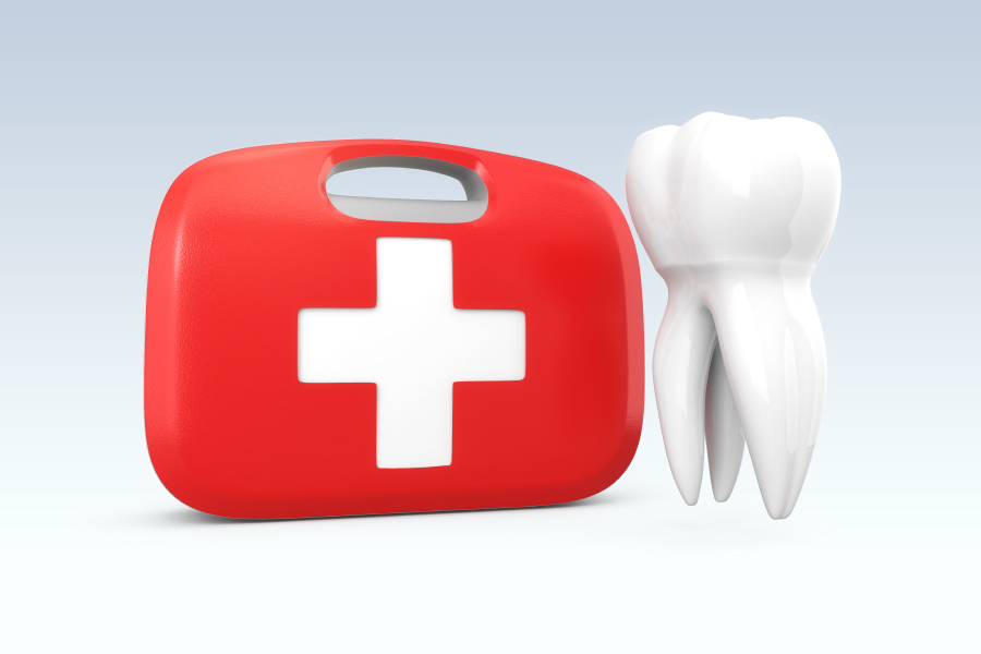 A tooth next to a red first aid kid to indicate a dental emergency