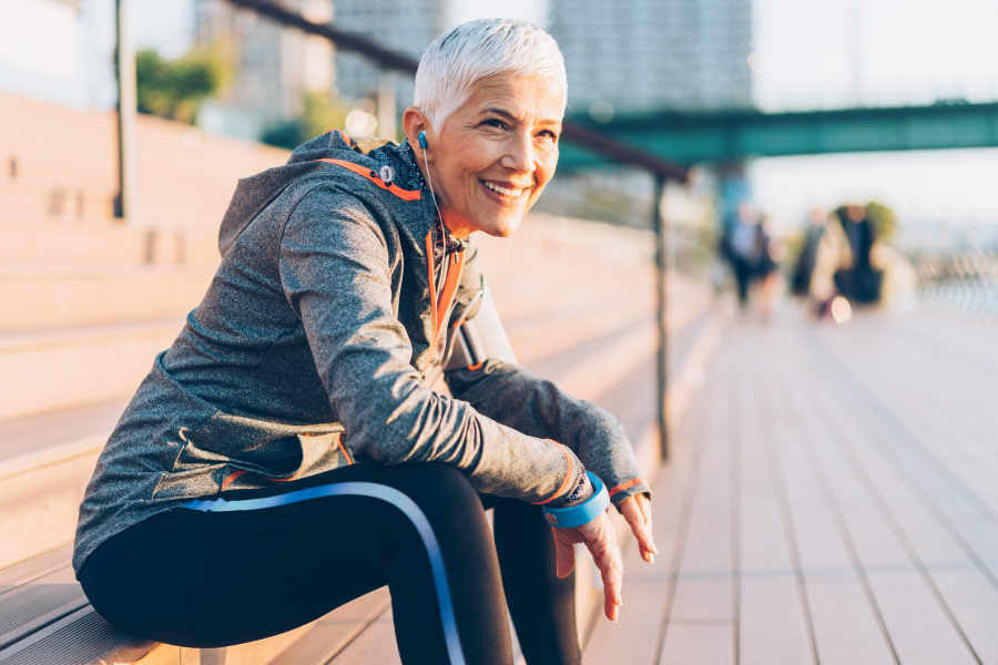 Woman with a dental bridge smiles while taking a break from her run in the city